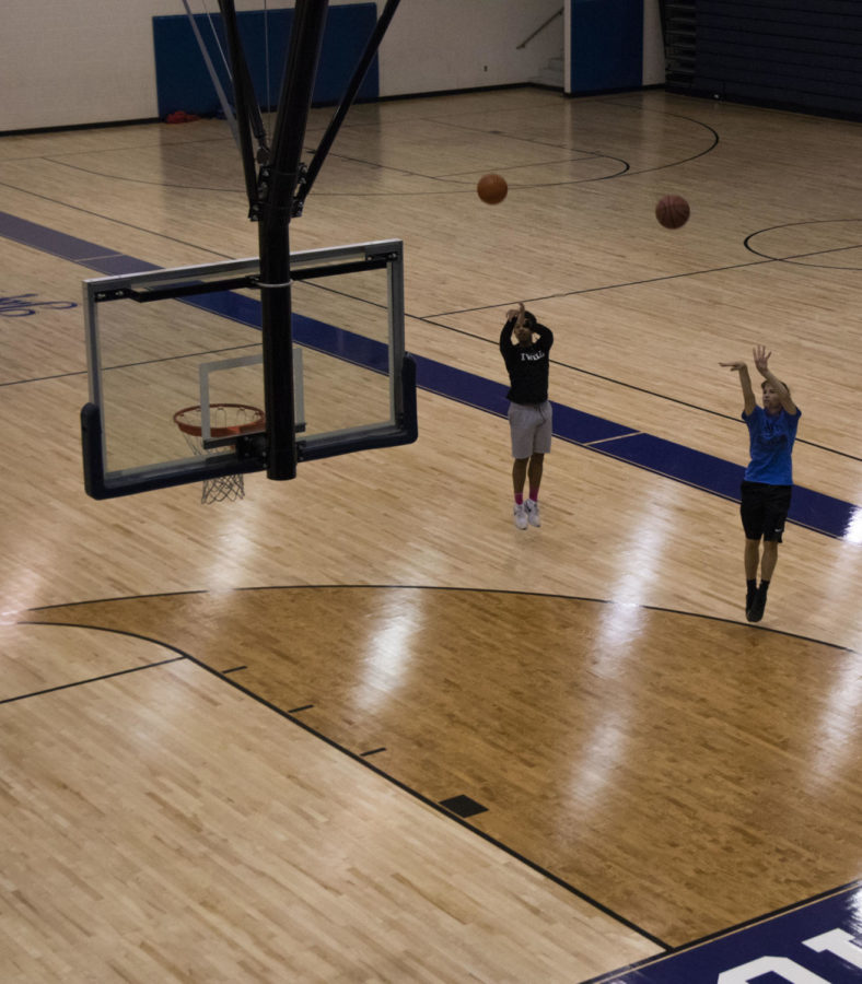 Students practice their 3-point shot in the Heider Center. The court got a new look over the summer with a complete redesign of the court markings.